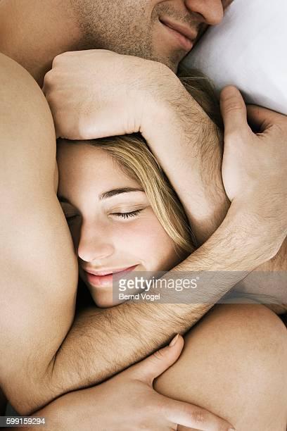 couple embracing in bed - oben ohne frau stock-fotos und bilder