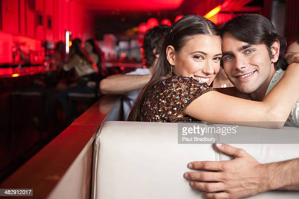 Couple embracing in booth at nightclub