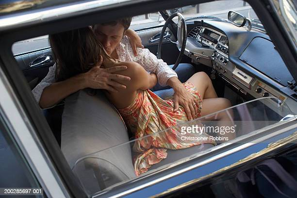 couple embracing in car, man's hand on woman's thigh, elevated view - leg kissing stock photos and pictures