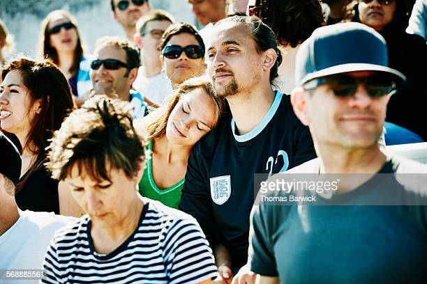 Couple embracing in crowd during soccer match
