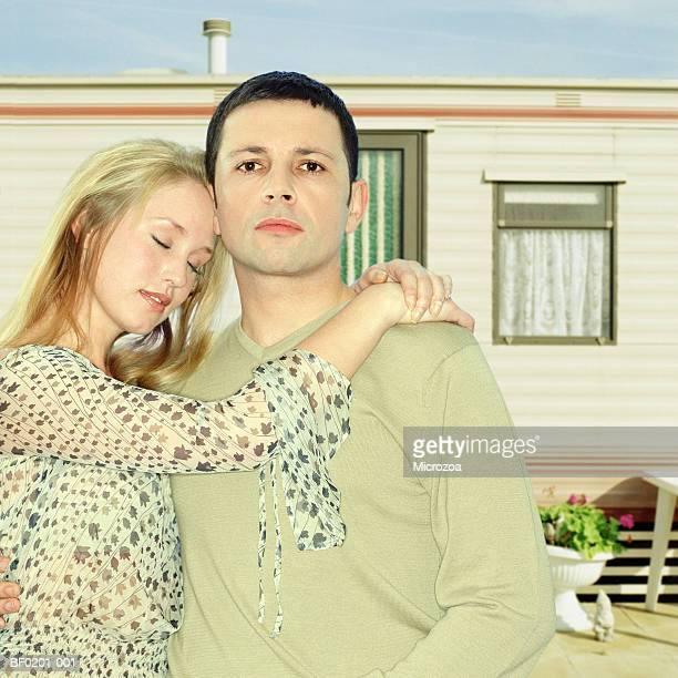 couple embracing in front of caravan, close-up, portrait - microzoa stock pictures, royalty-free photos & images