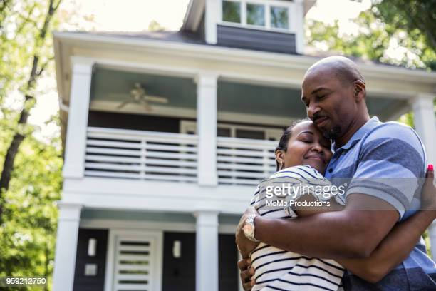 couple embracing in front of house - in front of stock pictures, royalty-free photos & images