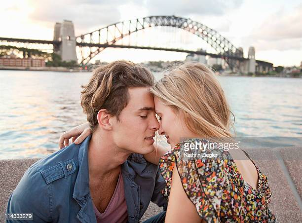 couple embracing in front of sydney harbour bridge - verliefd worden stockfoto's en -beelden