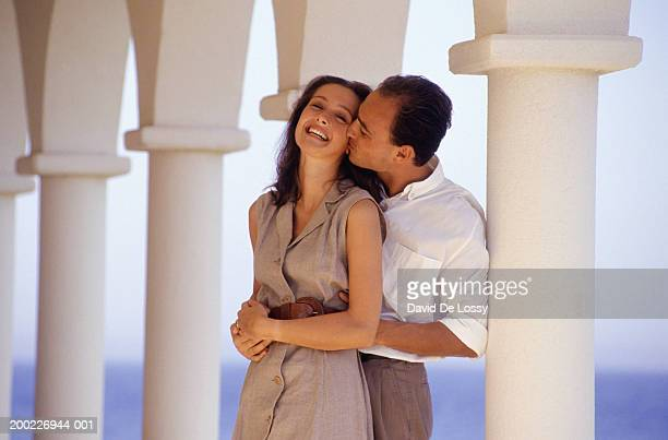 couple embracing in front of white columns, three quarter length - three quarter length ストックフォトと画像