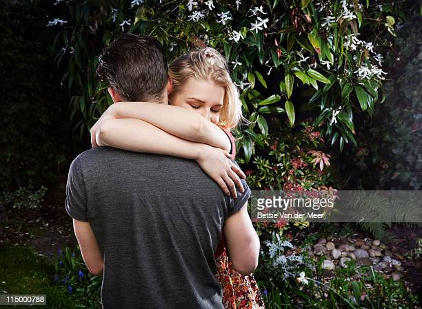 couple embracing in garden at night. - newpremiumuk stock pictures, royalty-free photos & images