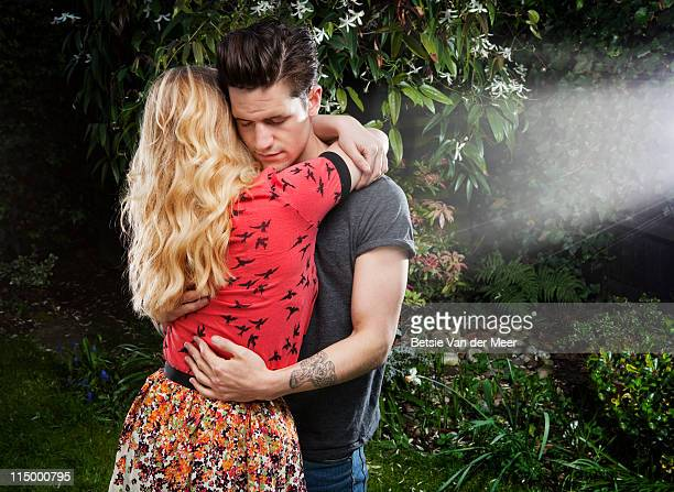 couple embracing in garden. - newpremiumuk stock pictures, royalty-free photos & images