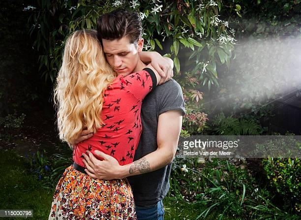 Couple embracing in garden.