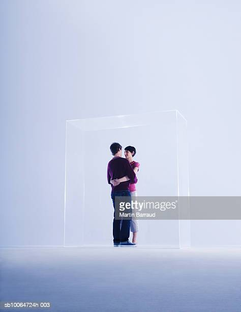 Couple embracing in glass cabinet