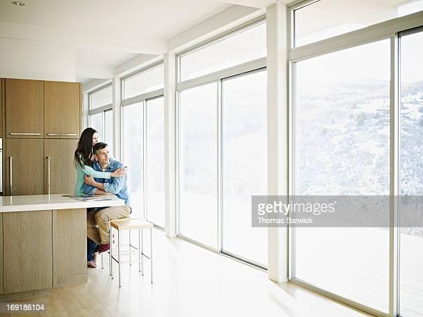 couple embracing in kitchen of modern home - finestra foto e immagini stock