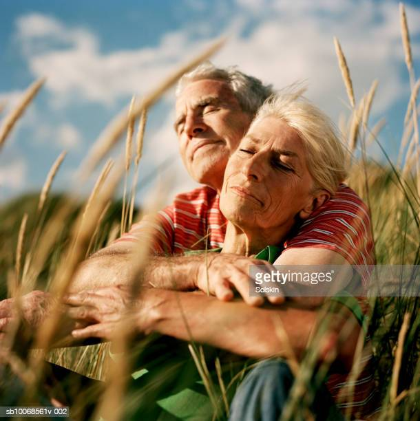 couple embracing in long grass - escapism stock pictures, royalty-free photos & images