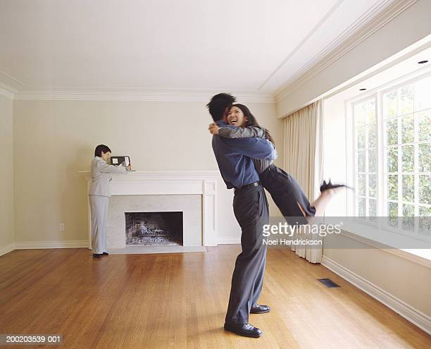 Couple embracing in new house, mature female realtor in background