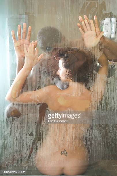 couple embracing in shower, naked, rear view - pareja ducha fotografías e imágenes de stock