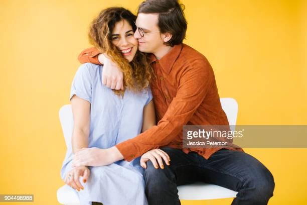 couple embracing in studio - vestito arancione foto e immagini stock