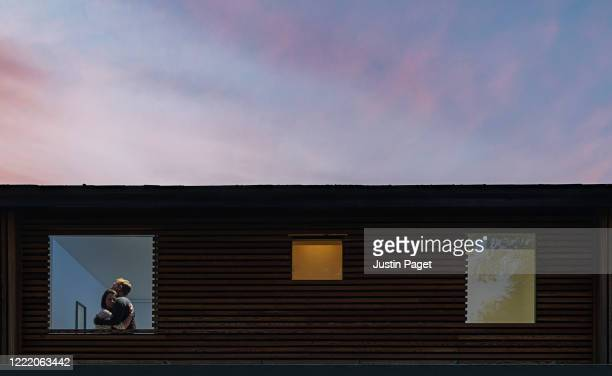 couple embracing in window at dusk - emotional stress stock pictures, royalty-free photos & images