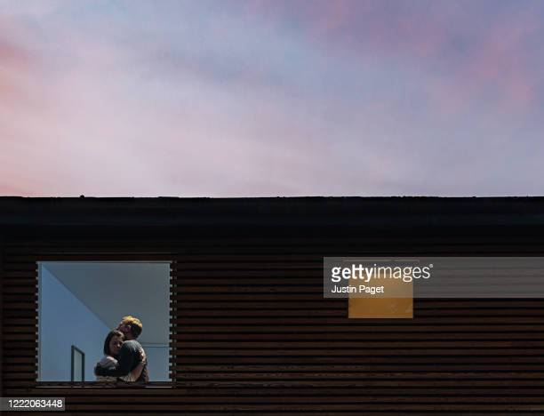 couple embracing in window at dusk - couple relationship stock pictures, royalty-free photos & images