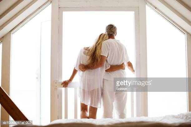couple embracing, looking out of bedroom window - holiday villa stock pictures, royalty-free photos & images