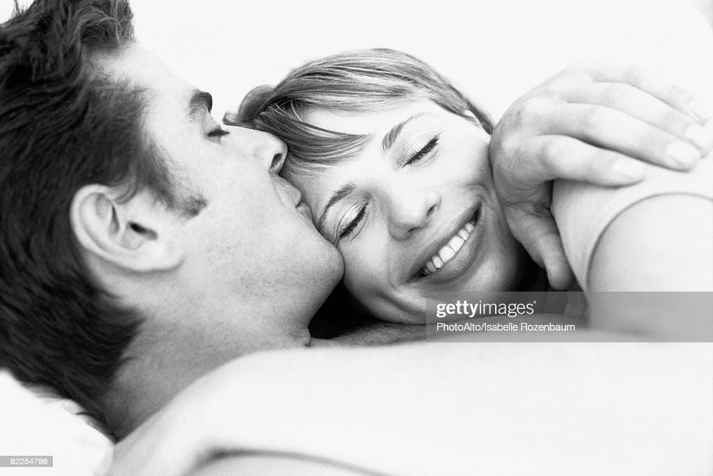 Couple embracing, man kissing woman's forehead, woman's eyes closed : Stock Photo