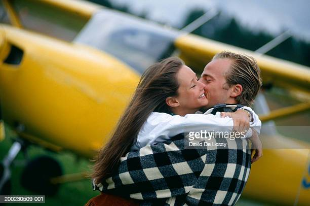 Couple embracing near small aircraft