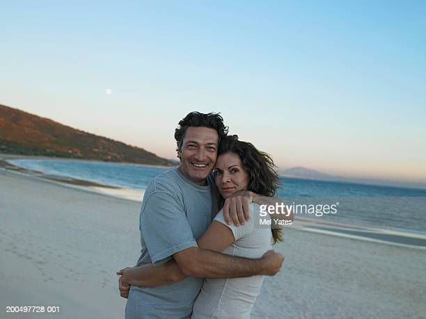 Couple embracing on beach, dusk, portrait, close-up