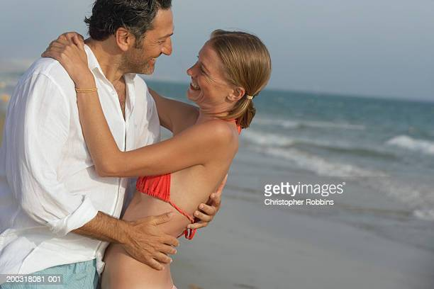 Couple embracing on beach, smiling at each other
