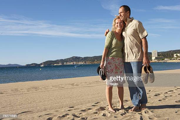 Couple embracing on beach with shoes off