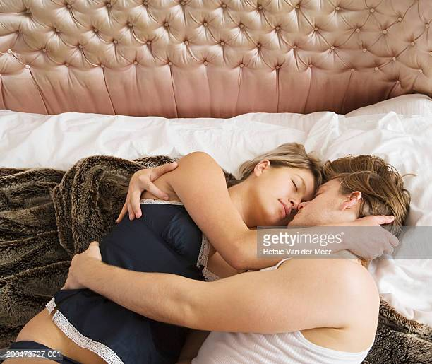 couple embracing on bed - romantic young couple sleeping in bed stock photos and pictures