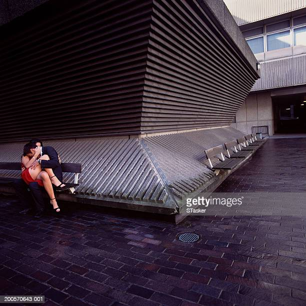 Couple embracing on bench, outdoors