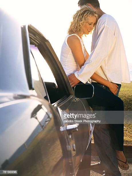 Couple embracing on car