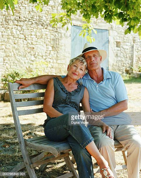 Couple embracing on chairs by house, portrait
