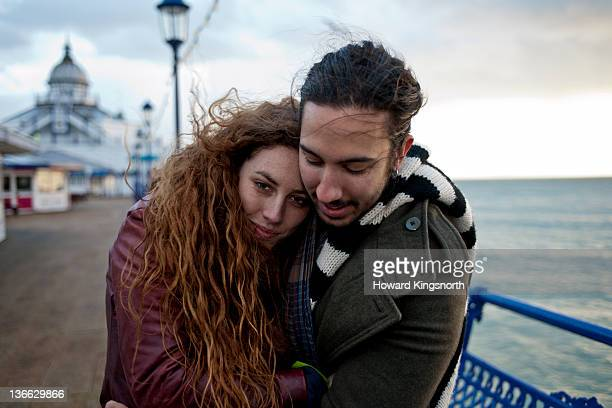 couple embracing on cold windswept pier