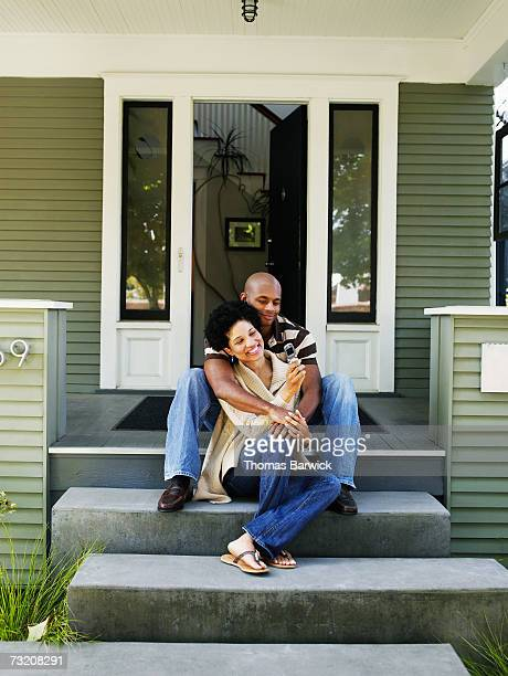 Couple embracing on front doorstep of home