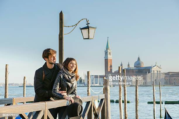 Couple embracing on pier in Venice lagoon sunset