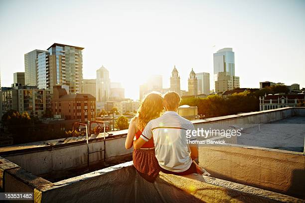 Couple embracing on rooftop at sunset rear view