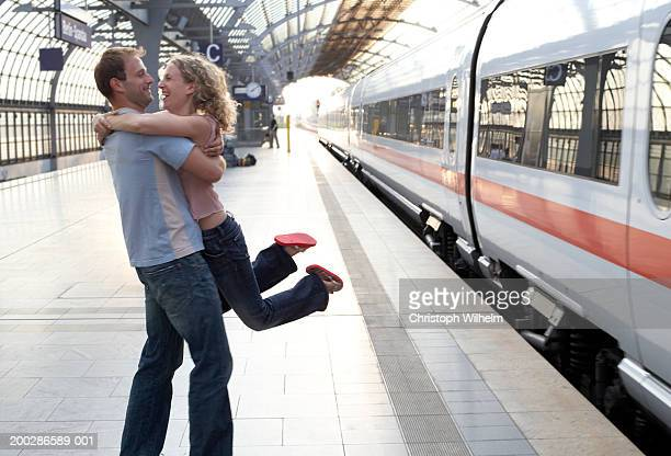 Couple embracing on station platform, man lifting woman, side view