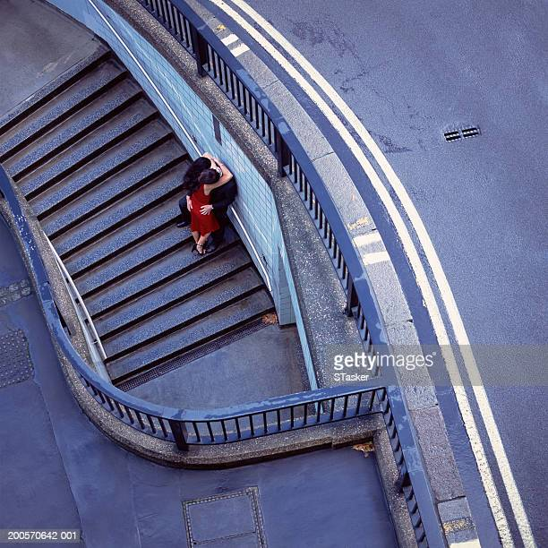 Couple embracing on steps beside road