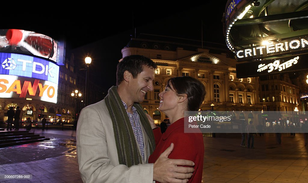 Couple embracing on street, smiling, side view, night : Stock-Foto