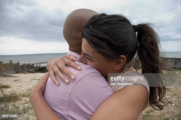 couple embracing on the beach - kent england stock pictures, royalty-free photos & images