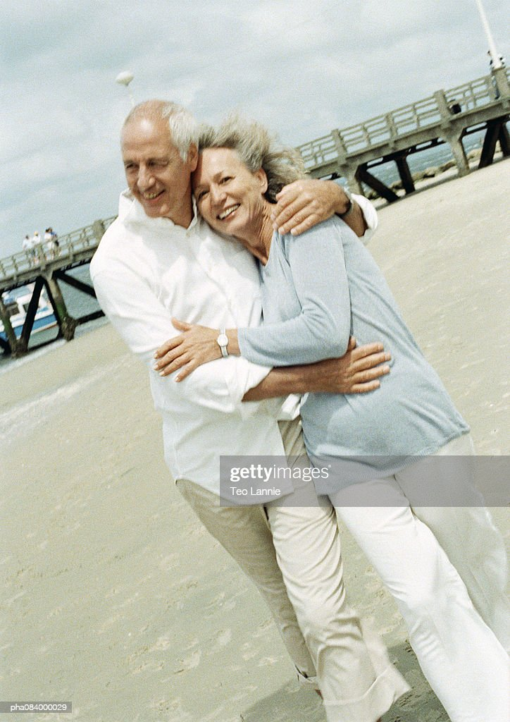 Couple embracing on the beach, smiling at camera. : Stockfoto
