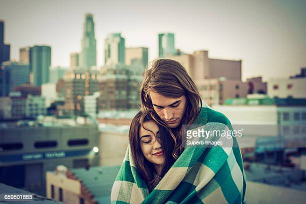 Couple embracing on urban rooftop
