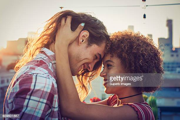 couple embracing on urban rooftop - romanticism stock pictures, royalty-free photos & images