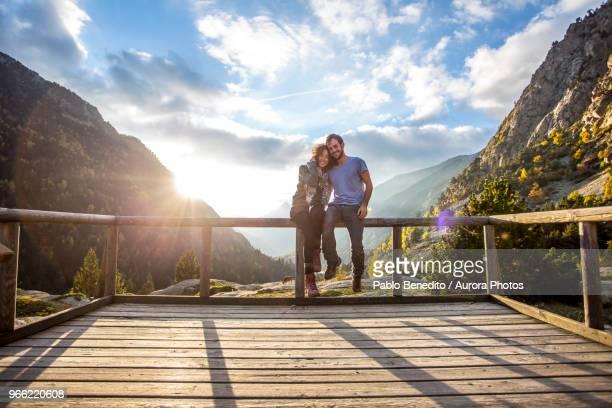 couple embracing on wooden platform in aiguestortes i estany de sant maurici national park, aiguestortes, lleida, spain - provinz lerida stock-fotos und bilder