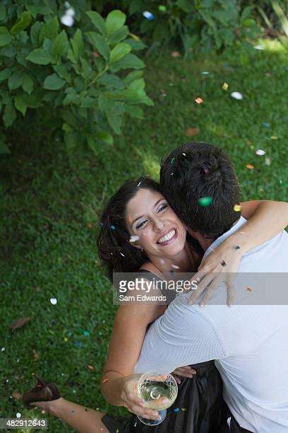 Casal experimentando ao ar livre com vinho branco e Confete sorridente