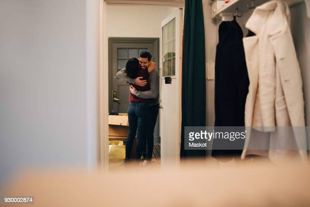 Couple embracing seen from doorway in new apartment
