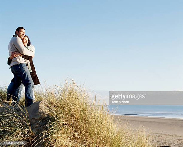 Couple embracing, standing in long grass on sand dune, low angle view