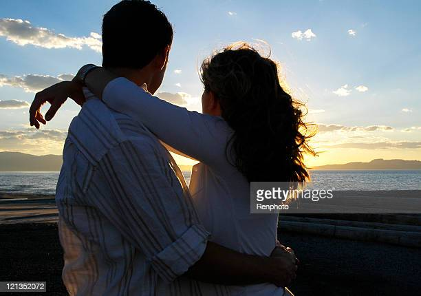 Couple Embracing Watching the Sunset