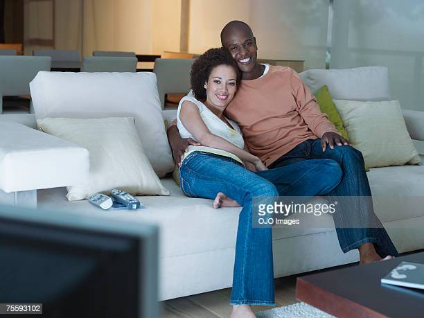 A couple embracing watching the television
