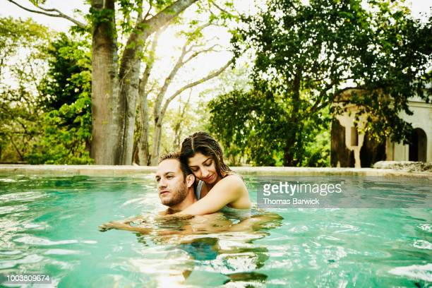 Couple embracing while relaxing in plunge pool at luxury resort