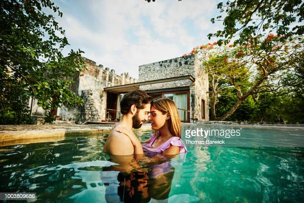 Couple embracing while relaxing in plunge pool outside of bungalow at luxury tropical resort