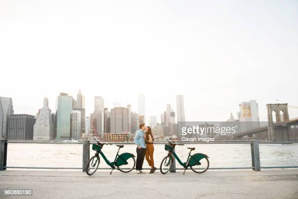 Couple embracing while standing by bicycles against East river in city