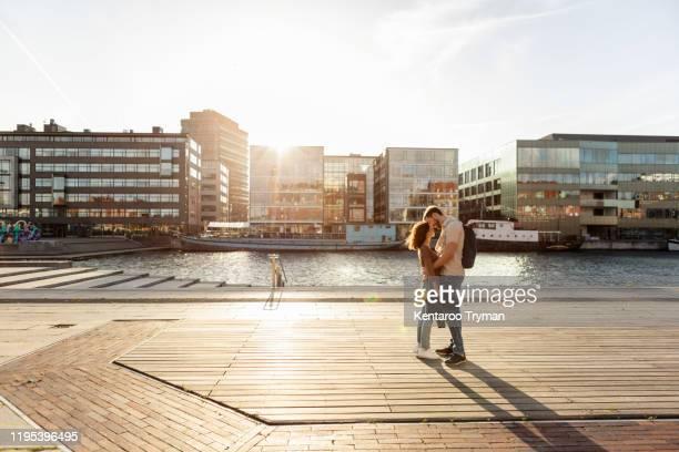 couple embracing while standing on promenade in city during summer - uferpromenade stock-fotos und bilder